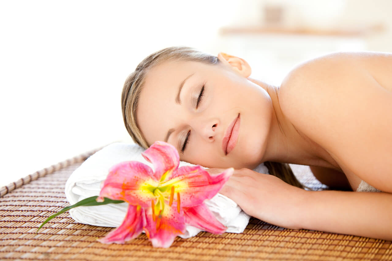 Woman lying on mat with flower
